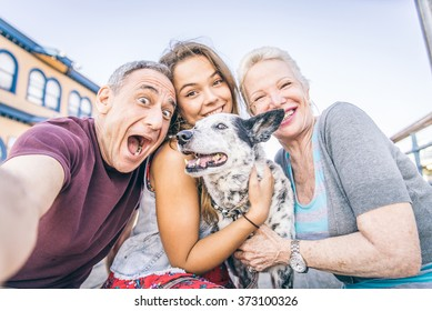 Self portrait of happy family with dog having fun outdoors - Grandparents and nephew taking a selfie