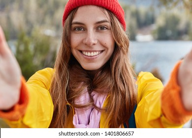 Self portrait of happy girl with European appearance, charming smile, wears red hat and yellow anorak, explores world while wanders, spends spare time alone with nature, satisfied by trip, has joy.