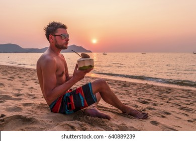 self portrait happy man traveler on the beach with coconut drink watching the sunset, attractive young men in swimwear shirtless on the beach, travel tourism concept, Pattaya Bangsaray Thailand