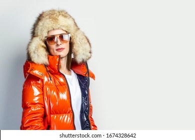 self portrait of a happy young girl in a red jacket and a fur hat on a light background. Fashion concept, shopping
