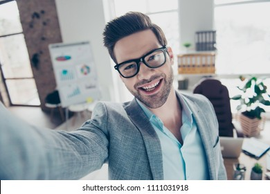 Self portrait of joyful funny man in shirt and jacket making selfie on smart phone with hand, standing in workplace