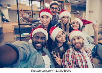 Self portrait of mixed race friends : african, american, asian, caucasian,  young smiling bearded men and beautiful women in red christmas hat showing peace symbol  to the camera, celebrating new year