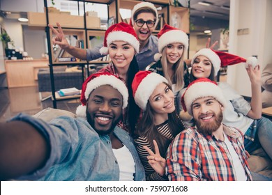 Self portrait of mixed race friends : african, american, asian, caucasian,  young smiling bearded men and beautiful women in red christmas hat posing to the camera, celebrating new year in the office