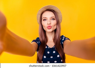 Self portrait of nice, amazing, pretty, positive, sexy woman shooting selfie in two hands on front camera, blowing air kiss to her boyfriend, having polka-dot outfit, isolated on yellow background