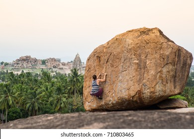 (Self) Portrait of photographer bouldering in south India with temples in the background.