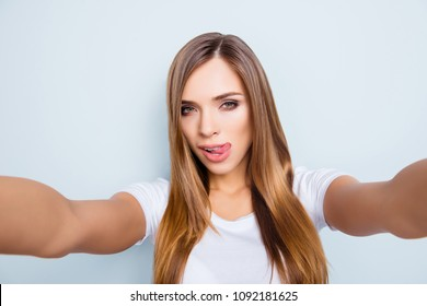 Self portrait of pretty bitch sexy pretty girl shooting selfie on front camera with two hands  isolated on grey background gesturing tongue out
