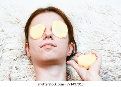 Self portrait: Redhead model using potato slices to relieve the dark circles under her tired and puffy eyes