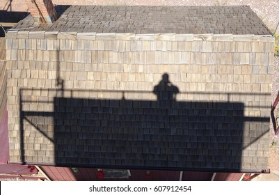 Self portrait as a shadow on the rooftop of a fire tower ranger residence as taken from the fire tower; Tonto National Forest in Arizona