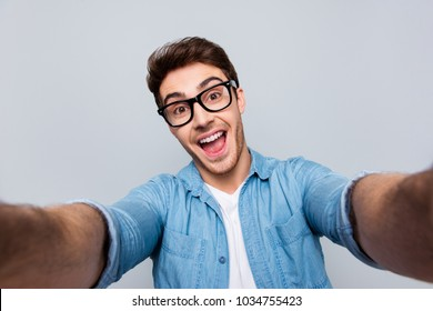 Self portrait of shouting screaming crazy funny man with open mouth, stubble in jeans shirt shooting selfie on front camera with two hands, having video call, isolated on grey background