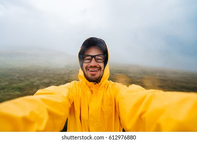 Self portrait of a smiling and laughing traveler man in yellow raincoat and glasses in the clouds mountains in stormy weather with rain