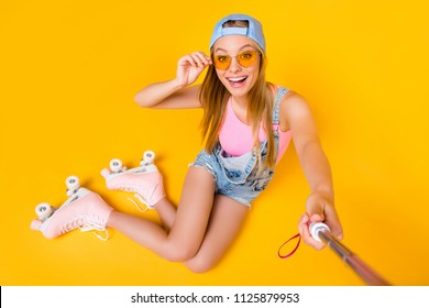 Self portrait of toothy joyful girl shooting selfie on front camera sitting on floor ground wearing roller skates isolated on yellow background, photography concept