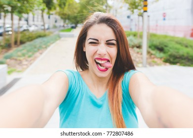 self portrait young woman mixed race outdoors tongue sticking out - happiness, having fun, youth culture concept