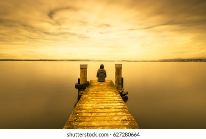 Self reflection in magical world of fantasy.  Woman sits on a wooden pier. Cloudy above the lake. Long exposure.