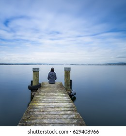 Self reflection. One woman sits on a wooden pier. Cloudy above the lake. Long exposure