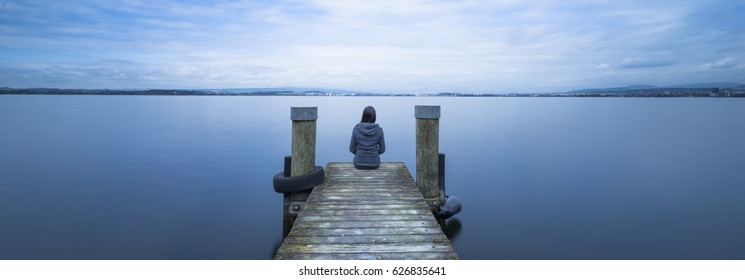 Self reflection. Woman sits on a wooden pier. Cloudy  lake. Long exposure.