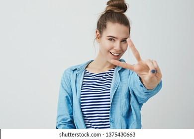 Self-assured determined woman ready achieve goal feeling lucky awesome, unstoppable desire win, confident upbeat white background, extending hand showing victory, peace gesture smiling daring