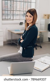 Self-assured friendly young businesswoman sitting perched on an office table with folded arms smiling at the camera