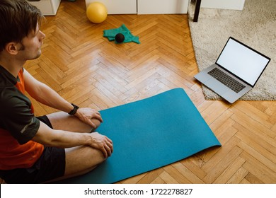 Self-care during stay at home COVID-19 Online yoga classes, Stretching exercises. Man at home with laptop. Attractive guy lying on fitness mat internet video online training blank laptop