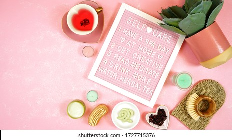 Self-care wellbeing home spa letterboard with herbal hibiscus tea, pro environmental plastic free beauty products and moisturisers on feminine pink background. Negative copy space.