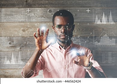 Self-confident black scientist in glasses and pink shirt using futuristic touchscreen display, drawing charts and diagrams, looking at the camera. People and future technology concept. Double exposure