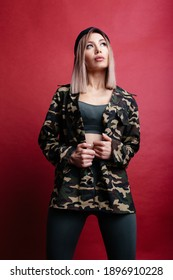 Self-confident blonde woman in khaki jacket standing over the red background and looking up. Sexy sporty woman