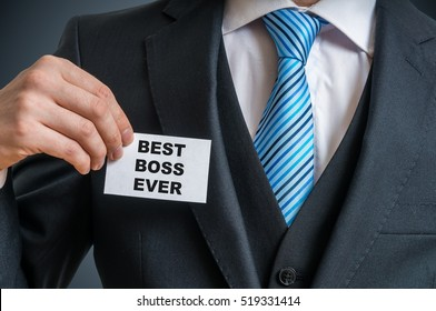 Self-confident businessman in suit is showing label that he is the best boss ever.