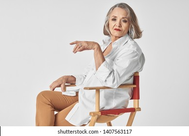 self-confident elderly woman sitting on a chair, side view beautiful face