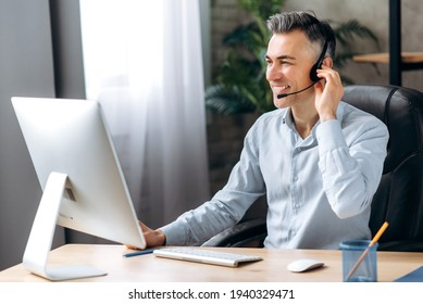 A self-confident European adult ceo, business leader, top manager communicates by video conference, conducts online briefing with colleagues, uses headset and computer, friendly smiling - Shutterstock ID 1940329471