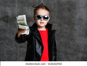 Self-confident generous rich kid boy millionaire in sunglasses, leather jacket and red t-shirt handing us a bundle of money cash, donating on urban concrete wall background