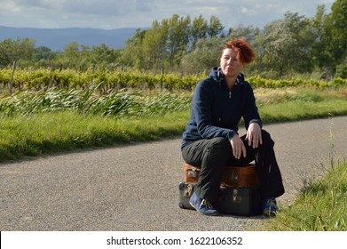 selfconfident red-haired woman on vacation sitting on her suitcases on a road and waiting