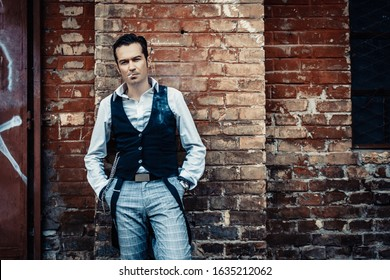 Self-confident retro-styled man smoking while leaning on brick wall with hands n pockets and looking at camera.