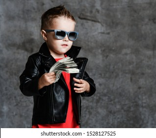 Self-confident rich kid boy in sunglasses, leather jacket and red t-shirt holding a bundle of dollars cash demonstrates superiority on concrete wall background with free copy space