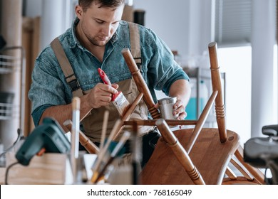 Self-employed carpenter painting wooden chair at carpentry