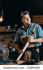 Self-employed handyman in work suit holding wooden board in his own carpentry