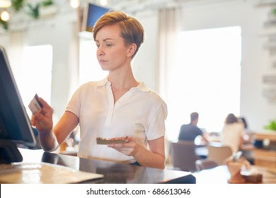 Self-employed merchant of coffee-shop registrating payment of client in electronic cashier