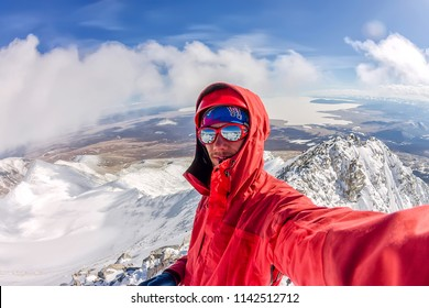 Selfi male mountaineer in snowy mountains, wearing a helmet with a backpack