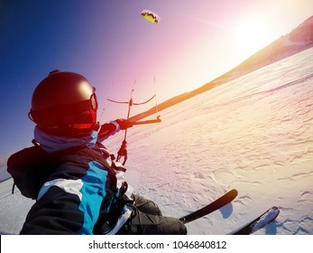 Selfie action camera Skier with kite rides on frozen lake on free ride. Russia. Snowkite sunset.