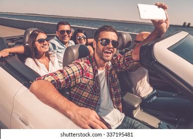 Selfie again! Group of young happy people enjoying road trip in convertible and making selfie