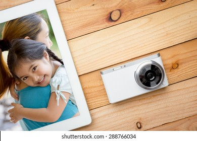 Selfie of asian daughter and mother on the screen of tablet computer with digital camera on wooden table