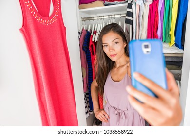 Selfie Asian girl taking photo with phone of outfit in walk-in closet dressing room. Clothes matching style. Shopping girl using smartphone fashion app posting on social media.