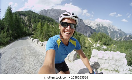 SELFIE: Awesome selfie shot of happy Caucasian man riding bicycle through the sunny mountains. Young male athlete having fun during challenging mountain bike race. Happy cyclist enjoying bike ride.