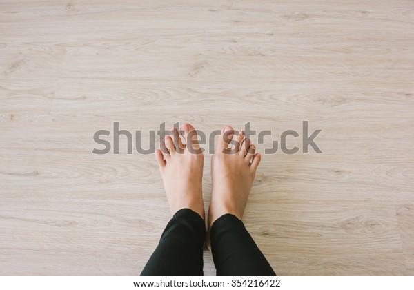 Selfie of bare feet on wooden floor background, top view