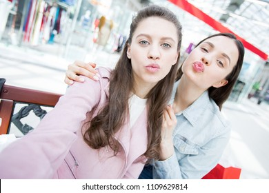 Selfie of beautiful fashion student girls puckering lips while posing for photo in shopping mall, brunette woman embracing friend