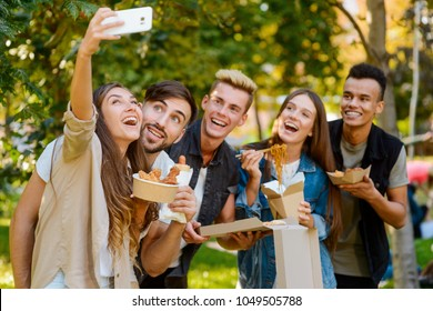 Selfie with best friends. Bunch of young people capturing happy moment, spending weekend in the park and eating fast food.