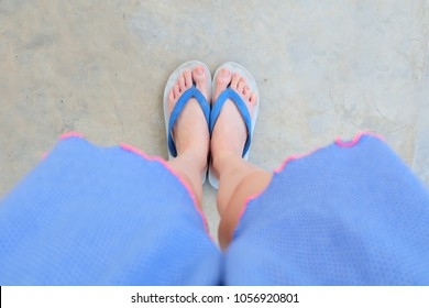 Selfie Blue Shoes Isolated on Concrete Floor for Top View. Woman's Feet Wearing Blue Pajamas and Flip Flop (Slippers) on The Cement Floor Background Great For Any Use.