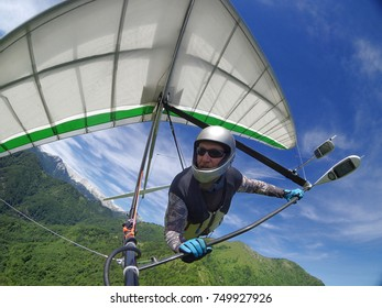 Selfie of brave extreme hang glider pilot soaring the thermal updrafts above green mountain hills taken with action camera