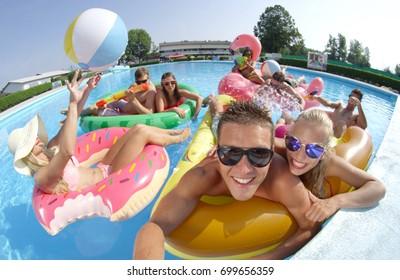 SELFIE: Cheerful smiling friends making selfie on fun colorful floaties in pool