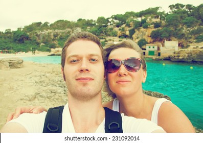 Selfie. Couple taking picture on the beach. Vintage effect photo.