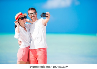 Selfie couple taking pictures on the beach. Tourists people taking travel photos on their holidays.