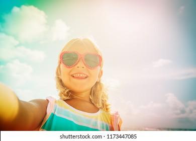 selfie of cute happy little girl at beach